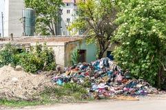 被放弃的农村损坏的房子在新的居民住房附近的少数民族居住区在当与破烂物和废弃物的垃圾堆使用的城市 免版税库存照片