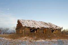 被放弃的原木小屋在冬天 免版税库存图片