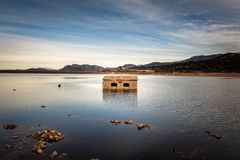 被放弃的和部分地被淹没的石大厦在惊叹的湖 库存照片