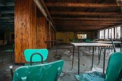 被放弃的大厦内部,有桌的大餐厅和椅子 库存照片