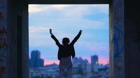 被放弃的大厦的少年享有生活的在微明,手上升了,城市 股票视频