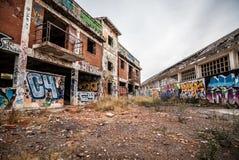 被放弃的工厂,毁坏与在墙壁上的街道画 库存照片
