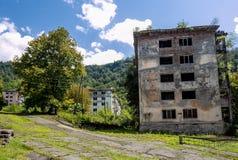 被放弃的开采的鬼魂镇Polyana,阿布哈兹 被毁坏的空的房子 免版税库存照片