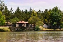 被放弃的房子在森林里,在湖边缘 免版税库存图片
