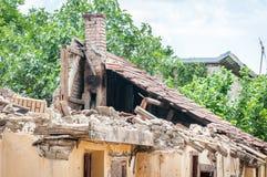 被放弃的房子的损坏的和打破的倒塌的屋顶在火以后的从与瓦片和喜怒无常的天空背景的手榴弹炸弹 免版税库存照片