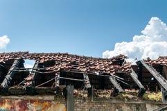 被放弃的房子的损坏的和打破的倒塌的屋顶在火以后的从与瓦片和蓝天背景的手榴弹炸弹 库存照片