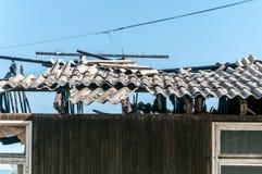 被放弃的房子的损坏的和打破的倒塌的屋顶在火以后的从与瓦片和蓝天背景的手榴弹炸弹 免版税图库摄影