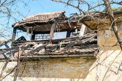 被放弃的房子的损坏的和打破的倒塌的屋顶在火以后的从手榴弹炸弹,与瓦片和蓝天背景 免版税库存图片