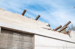 被放弃的房子的损坏的和打破的倒塌的屋顶在火以后的从手榴弹炸弹,有残破的窗口和蓝天背景 免版税库存照片