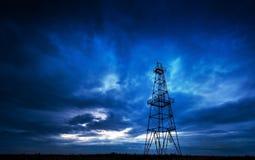 被放弃的抽油装置、严重的云彩和夜间天空 库存图片