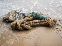 被放弃的捕鱼网和绳索在海滩 图库摄影