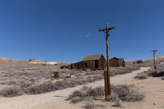 以被放弃的木大厦为背景的输电线 免版税库存照片