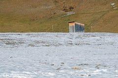 被放弃的木棚子在积雪的村庄在冬日 免版税库存照片
