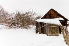 被放弃的木棚子在积雪的村庄 免版税库存照片
