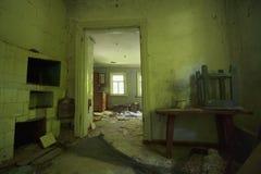 被放弃的村庄私有房子在Pripyat :绿色墙壁,老俄国火炉,在那里木桌上是一把被倒置的凳子, crumpl 免版税库存照片