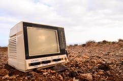 被放弃的残破的灰色电视 免版税库存图片