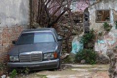 被放弃的汽车和被破坏的墙壁 库存照片