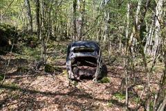 被放弃的汽车在法国森林里 库存照片