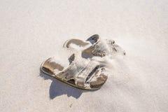 被放弃的海滩凉鞋 图库摄影