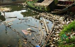 被放弃的渔船和许多塑料废物 库存照片