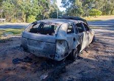 被放弃的烧坏的汽车小型客车后方右边 免版税库存图片