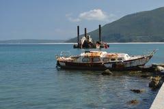 被放弃的生锈的小船和老挖泥机 图库摄影