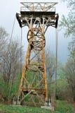 被放弃的生锈的空中览绳柱子在森林里 库存图片
