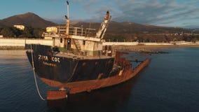 被放弃的生锈的船特写镜头搁浅反对美好的日落天空、山和海岸线 ?? 老在大洋里航行 股票录像