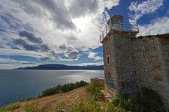 被放弃的石灯塔在剧烈的天空下,希腊 免版税库存照片