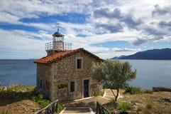 被放弃的石灯塔在剧烈的天空下,希腊 库存图片