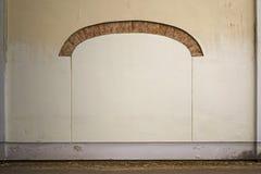 被放弃的破裂的灰泥砖墙有曲拱框架背景 免版税库存图片