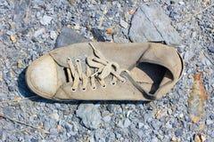 被放弃的老帆布鞋损坏了 免版税库存照片