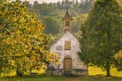 被放弃的老教会和秋天树 免版税库存图片