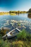 被放弃的老木渔船在Summer湖或河 美好的夏天晴天 免版税库存照片