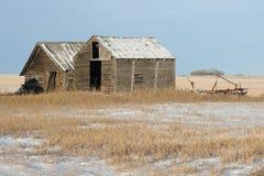 被放弃的老棚子和农业机械在冬天 免版税图库摄影