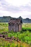 被放弃的老毁坏一个绿色领域的一个谷仓 免版税库存图片