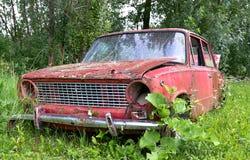 被放弃的老汽车在草甸 库存图片