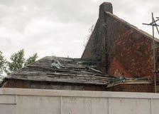 被放弃的老烧在有门的房子下在它附近 库存照片