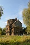 被放弃的被毁坏的木教会在北俄国村庄 免版税库存照片