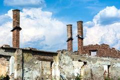 被放弃的被毁坏的老家庭砖房子没有屋顶和有烟囱的 图库摄影