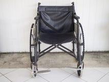 被放弃的轮椅和白色墙壁backgroundabandoned轮椅和白色墙壁背景 免版税图库摄影
