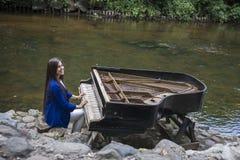 被放弃的gran钢琴,由一条河岸Vilnia河的减少钢琴Uzupis艺术家的在维尔纽斯,立陶宛,捷克人扎营 免版税库存照片