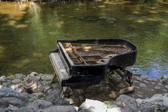 被放弃的gran钢琴,由一条河岸Vilnia河的减少钢琴Uzupis艺术家的在维尔纽斯,立陶宛,捷克人扎营 免版税图库摄影