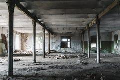 被放弃的wharehouse工厂厂房内部在暗色的 免版税库存图片