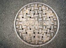 被放气的出入孔下水渠盖子沥青四德街水流失 免版税图库摄影