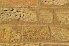 被日光照射了一个的石墙 免版税图库摄影