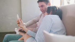 被日光照射了年轻夫妇坐长沙发,显示某事的女孩对智能手机的一个人 库存照片