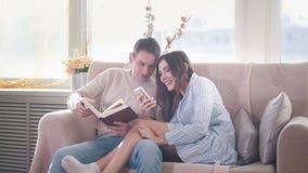 被日光照射了年轻夫妇坐长沙发,显示某事的女孩对智能手机的一个人 库存图片