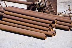 被日光照射了棕色工业铁用管道输送堆 库存图片