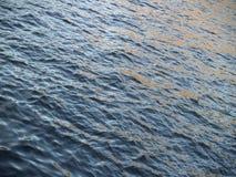 被日光照射了的河的挥动的表面 免版税库存照片